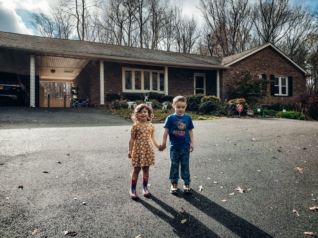 young kids in front of the house